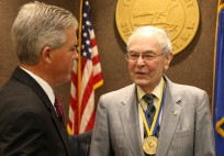 Suffolk County Executive Steve Bellone gives master planner Lee Koppelman the Suffolk Medal for Distinguished Service in Hauppauge on July 20. (Phot
